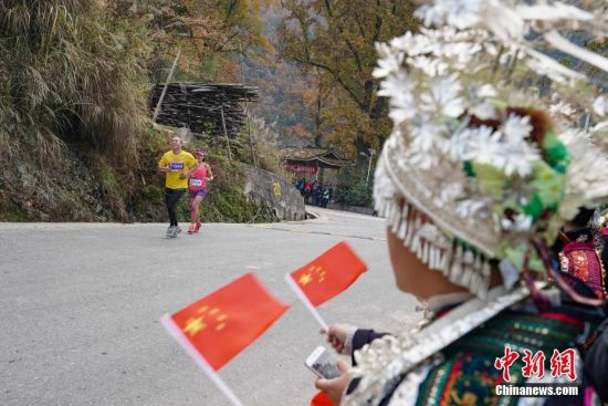 图为比赛选手经过苗寨赛道时,苗族民众盛装载歌载舞,夹道为参赛选手加油。中新社记者 贺俊怡 摄