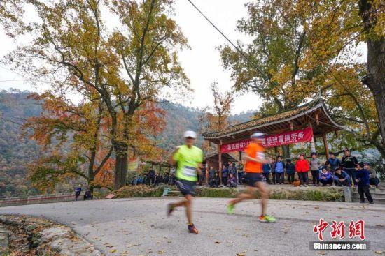 图为选手从贵州台江苗寨外赛道经过。中新社记者 贺俊怡 摄