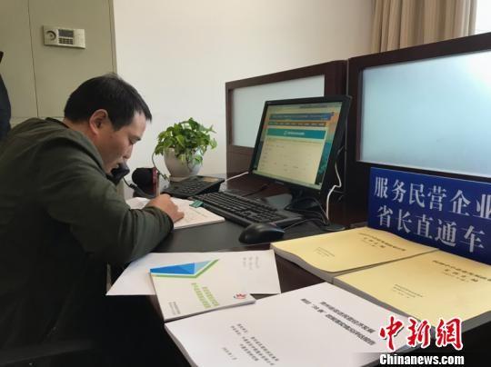"""贵州省""""服务民营企业省长直通车""""办公室工作人员陈永朋正在接听电话。 冷桂玉 摄"""