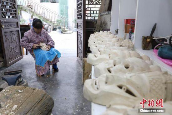 """""""傩堂戏""""是土家族的一种祭祖活动,具有悠久的历史。傩面具作为""""傩堂戏""""重要的组成部分,手工制作工序繁多,共涉及取材、制坯、雕刻、打磨、着色、上漆成品6个流程、20多道工序。今年40岁的土家族女子杨云霞是贵州省铜仁市沿河土家族自治县甘溪乡沙坝村杨家傩戏面具雕刻技艺的第七代传承人。中新社记者 瞿宏伦 摄"""