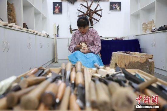 """""""傩堂戏""""是土家族的一种祭祖活动,具有悠久的历史。傩面具作为""""傩堂戏""""重要的组成部分,手工制作工序繁多,共涉及取材、制坯、雕刻、打磨、着色、上漆成品6个流程、20多道工序。今年40岁的土家族女子杨云霞是贵州省铜仁市沿河土家族自治县甘溪乡沙坝村杨家傩戏面具雕刻技艺的第七代传承人。图为12月2日,杨云霞在用刻刀雕刻傩面具。图为中新社记者 瞿宏伦 摄"""
