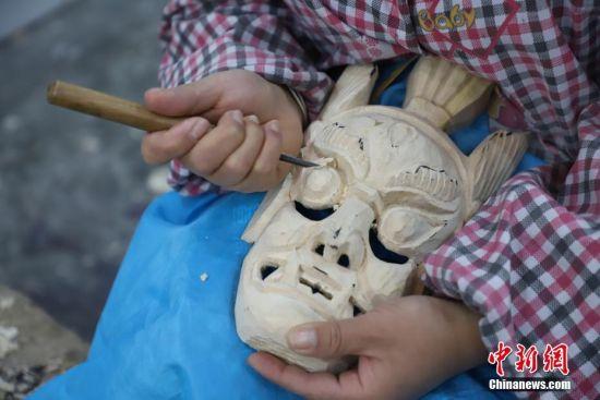 """""""傩堂戏""""是土家族的一种祭祖活动,具有悠久的历史。傩面具作为""""傩堂戏""""重要的组成部分,手工制作工序繁多,共涉及取材、制坯、雕刻、打磨、着色、上漆成品6个流程、20多道工序。今年40岁的土家族女子杨云霞是贵州省铜仁市沿河土家族自治县甘溪乡沙坝村杨家傩戏面具雕刻技艺的第七代传承人。图为杨云霞用刻刀雕刻傩面具。中新社记者 瞿宏伦 摄"""