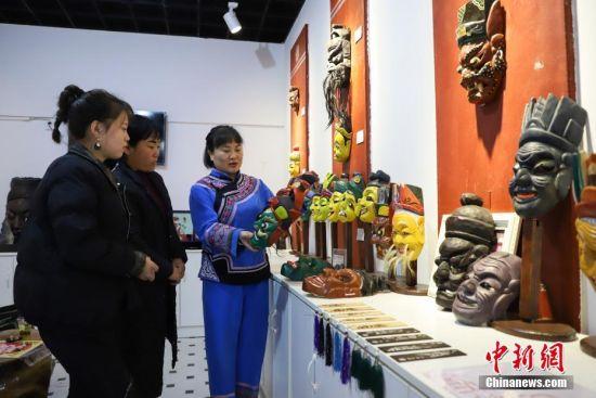 """""""傩堂戏""""是土家族的一种祭祖活动,具有悠久的历史。傩面具作为""""傩堂戏""""重要的组成部分,手工制作工序繁多,共涉及取材、制坯、雕刻、打磨、着色、上漆成品6个流程、20多道工序。今年40岁的土家族女子杨云霞是贵州省铜仁市沿河土家族自治县甘溪乡沙坝村杨家傩戏面具雕刻技艺的第七代传承人。图为杨云霞给参观者介绍她雕刻的傩面具。中新社记者 瞿宏伦 摄"""