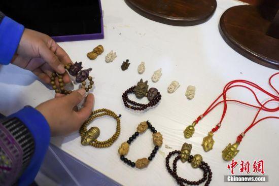 """""""傩堂戏""""是土家族的一种祭祖活动,具有悠久的历史。傩面具作为""""傩堂戏""""重要的组成部分,手工制作工序繁多,共涉及取材、制坯、雕刻、打磨、着色、上漆成品6个流程、20多道工序。今年40岁的土家族女子杨云霞是贵州省铜仁市沿河土家族自治县甘溪乡沙坝村杨家傩戏面具雕刻技艺的第七代传承人。图为杨云霞整理傩面具文化工艺品和小型微雕作品。中新社记者 瞿宏伦 摄"""