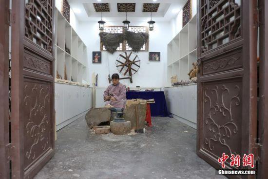 """""""傩堂戏""""是土家族的一种祭祖活动,具有悠久的历史。傩面具作为""""傩堂戏""""重要的组成部分,手工制作工序繁多,共涉及取材、制坯、雕刻、打磨、着色、上漆成品6个流程、20多道工序。今年40岁的土家族女子杨云霞是贵州省铜仁市沿河土家族自治县甘溪乡沙坝村杨家傩戏面具雕刻技艺的第七代传承人。图为杨云霞制作傩面具的坯。中新社记者 瞿宏伦 摄"""