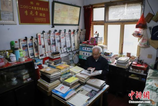 12月6日,李元章老人在翻阅资料。贵州省毕节市黔西县85岁老人李元章,从1958年开始就做起了新闻通讯员,至今已有60年。李元章每天坚持读报、写稿,60年里,他共向各大新闻媒体投稿6800余条。中新社记者 瞿宏伦 摄