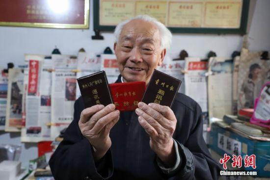 12月6日,李元章老人展示自己的通讯员证件。贵州省毕节市黔西县85岁老人李元章,从1958年开始就做起了新闻通讯员,至今已有60年。李元章每天坚持读报、写稿,60年里,他共向各大新闻媒体投稿6800余条。中新社记者 瞿宏伦 摄