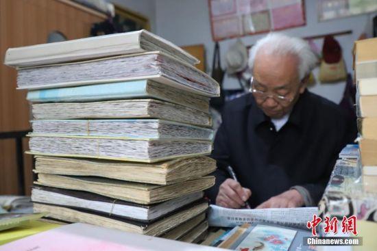 12月6日,李元章老人在标注报纸上的重点。贵州省毕节市黔西县85岁老人李元章,从1958年开始就做起了新闻通讯员,至今已有60年。李元章每天坚持读报、写稿,60年里,他共向各大新闻媒体投稿6800余条。中新社记者 瞿宏伦 摄