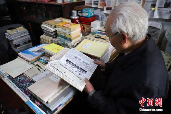 12月6日,李元章老人在翻看报纸的剪贴本。贵州省毕节市黔西县85岁老人李元章,从1958年开始就做起了新闻通讯员,至今已有60年。李元章每天坚持读报、写稿,60年里,他共向各大新闻媒体投稿6800余条。中新社记者 瞿宏伦 摄