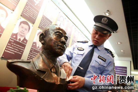 杨杰在贵州公安陈列馆,为父亲的铜像擦拭灰尘