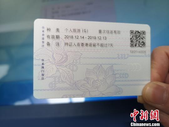 图为:赴港澳台再次签注一体机现场签注卡片式港澳台通行证。 赵万江 摄