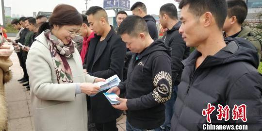 贵州省商务厅厅长季泓向贵州省首批赴澳门务工人员发放宣传资料。 曾实 摄