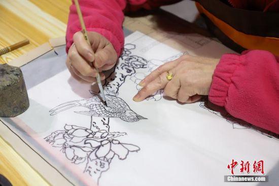 """12月16日,手绘""""通草堆画""""的设计图纸。""""通草堆画""""是贵州遵义的一种民间手工艺品,主要以药用植物――""""通草""""作为原材料。该技艺以素堆法为主,有设计、制图、切片、雕刻、成形等多道工序。""""通草堆画""""技艺于2007年被列为贵州省级非物质文化遗产,作为该项技艺传承人的左惠平和其儿子李跃在传承的基础上不断创新,使得产品远销海内外。中新社记者 瞿宏伦 摄"""