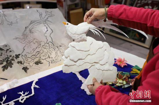 """12月16日,查看图纸确定""""通草堆画""""摆放的位置。""""通草堆画""""是贵州遵义的一种民间手工艺品,主要以药用植物――""""通草""""作为原材料。该技艺以素堆法为主,有设计、制图、切片、雕刻、成形等多道工序。""""通草堆画""""技艺于2007年被列为贵州省级非物质文化遗产,作为该项技艺传承人的左惠平和其儿子李跃在传承的基础上不断创新,使得产品远销海内外。中新社记者 瞿宏伦 摄"""