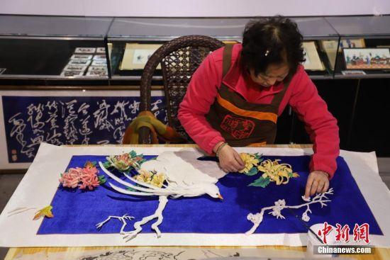 """12月16日,左惠平在贴合""""通草堆画""""。""""通草堆画""""是贵州遵义的一种民间手工艺品,主要以药用植物――""""通草""""作为原材料。该技艺以素堆法为主,有设计、制图、切片、雕刻、成形等多道工序。""""通草堆画""""技艺于2007年被列为贵州省级非物质文化遗产,作为该项技艺传承人的左惠平和其儿子李跃在传承的基础上不断创新,使得产品远销海内外。中新社记者 瞿宏伦 摄"""