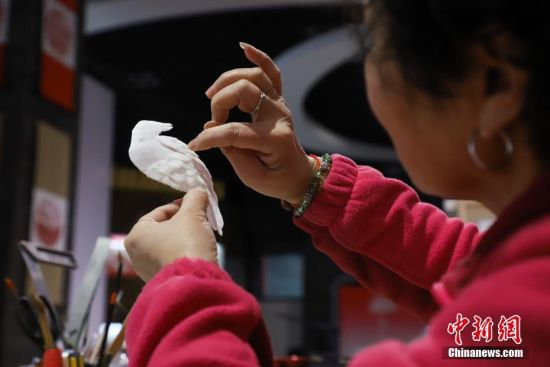 """12月16日,左惠平在查看半成品部件是否工整。""""通草堆画""""是贵州遵义的一种民间手工艺品,主要以药用植物――""""通草""""作为原材料。该技艺以素堆法为主,有设计、制图、切片、雕刻、成形等多道工序。""""通草堆画""""技艺于2007年被列为贵州省级非物质文化遗产,作为该项技艺传承人的左惠平和其儿子李跃在传承的基础上不断创新,使得产品远销海内外。中新社记者 瞿宏伦 摄"""