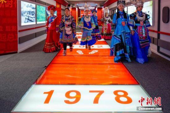 """12月18日,身着民族服饰的参观者在贵州省庆祝改革开放40周年大型展览现场观展。当日,以""""砥砺前行四十载・感恩奋进新时代""""为主题的贵州省庆祝改革开放40周年大型展览在贵州美术馆拉开帷幕。展览以实物、图文、图表、视频、浮雕、沙盘、模型、VR体验等多种形式,向民众展现贵州改革开放40年来的变迁。中新社记者 贺俊怡 摄"""