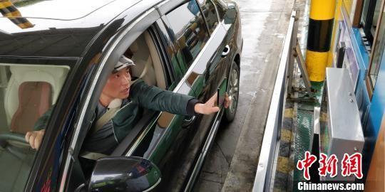 驾驶员通过收费站时使用微信支付高速通行费。 曾实 摄