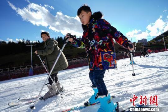 蓝天白云下,游客体验滑雪。 贺俊怡 摄