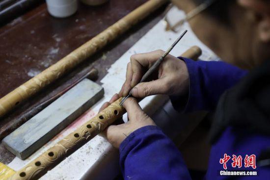 """1月10日,""""玉屏箫笛""""省级传承人吴继红在雕刻箫笛。产于贵州省铜仁市玉屏侗族自治县的""""玉屏箫笛""""是中国著名的传统竹管乐器,以音色清越优美、雕刻精致而著称。""""玉屏箫笛""""融合了当地侗、汉、苗、土家等多民族文化元素,经取材、制坯、雕刻、成品4大工艺流程数十道工序手工制作而成,玉屏箫笛制作技艺于2006年5月被列为第一批中国国家级非物质文化遗产名录。中新社记者 瞿宏伦 摄"""