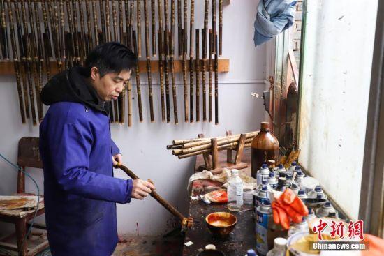 """1月10日,""""玉屏箫笛""""省级传承人吴继红在为箫笛上漆。产于贵州省铜仁市玉屏侗族自治县的""""玉屏箫笛""""是中国著名的传统竹管乐器,以音色清越优美、雕刻精致而著称。""""玉屏箫笛""""融合了当地侗、汉、苗、土家等多民族文化元素,经取材、制坯、雕刻、成品4大工艺流程数十道工序手工制作而成,玉屏箫笛制作技艺于2006年5月被列为第一批中国国家级非物质文化遗产名录。中新社记者 瞿宏伦 摄"""