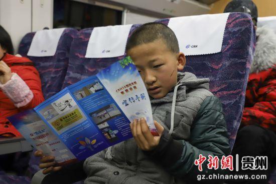 图为一名小旅客在阅读宣传手册。 瞿宏伦 摄