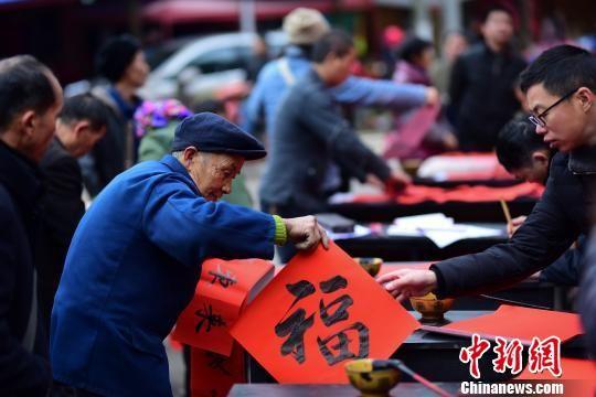"""图为村民在挑选书法爱好者写的春联和""""福""""字。 杨武魁 摄"""