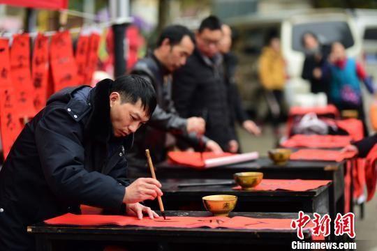 图为书法爱好者在集市上为村民写春联。 杨武魁 摄