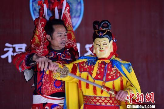 图为周昌智(左)在指导村民表演阳戏。 杨武魁 摄