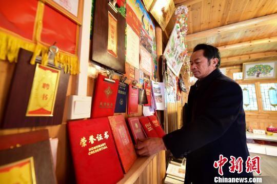 图为周昌智在家中整理多年来表演和传承福泉阳戏所获得的各类证书。 杨武魁 摄