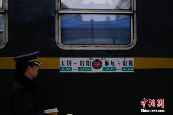 """1月17日,贵州玉屏火车站,凯里车务段外勤值班员姚本红在站台巡查。往返于贵州省贵阳市与铜仁市玉屏县的5639/5640次普速列车,全程342公里,行驶7个多小时,是人们常提到的""""绿皮火车"""",从1975年全线通车至今,这列火车已开行44年。在过去22年间,从未提高票价,区间内最低票价2元。列车穿行于贵州山区,沿线16个站连通很多少数民族村寨,目前仍是沿线民众赶集买卖,进城办事的重要交通工具。2019年春运期间,贵阳客运段5639/5640次、5629/5630次、5645/5646次列车不停运,方便沿线民众出行。中新社记者 贺俊怡 摄"""