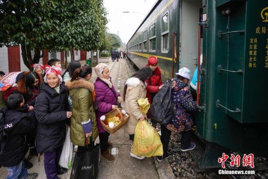 """1月17日,乘客在沿线一个小站排队登上开往贵阳的5639次列车。往返于贵州省贵阳市与铜仁市玉屏县的5639/5640次普速列车,全程342公里,行驶7个多小时,是人们常提到的""""绿皮火车"""",从1975年全线通车至今,这列火车已开行44年。在过去22年间,从未提高票价,区间内最低票价2元。列车穿行于贵州山区,沿线16个站连通很多少数民族村寨,目前仍是沿线民众赶集买卖,进城办事的重要交通工具。2019年春运期间,贵阳客运段5639/5640次、5629/5630次、5645/5646次列车不停运,方便沿线民众出行。中新社记者 贺俊怡 摄"""