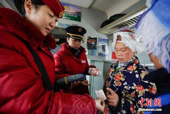 """1月17日,少数民族妇女在列车上购票,因列车停靠小站不设售票窗口,当地民众通常先上车后补票。往返于贵州省贵阳市与铜仁市玉屏县的5639/5640次普速列车,全程342公里,行驶7个多小时,是人们常提到的""""绿皮火车"""",从1975年全线通车至今,这列火车已开行44年。在过去22年间,从未提高票价,区间内最低票价2元。列车穿行于贵州山区,沿线16个站连通很多少数民族村寨,目前仍是沿线民众赶集买卖,进城办事的重要交通工具。2019年春运期间,贵阳客运段5639/5640次、5629/5630次、5645/5646次列车不停运,方便沿线民众出行。中新社记者 贺俊怡 摄"""