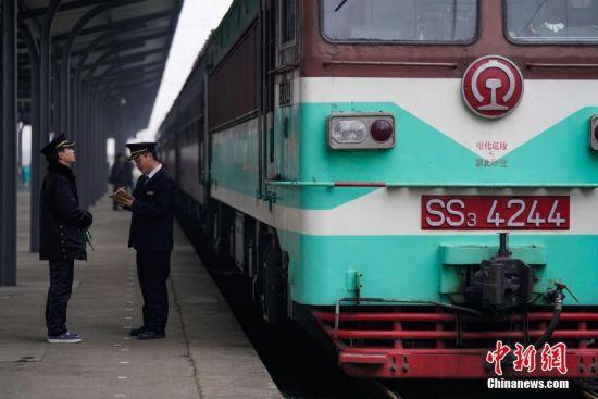 """1月17日,贵州玉屏火车站,凯里车务段外勤值班员姚本红(左)和开往贵阳的5639次司机进行工作交接。往返于贵州省贵阳市与铜仁市玉屏县的5639/5640次普速列车,全程342公里,行驶7个多小时,是人们常提到的""""绿皮火车"""",从1975年全线通车至今,这列火车已开行44年。在过去22年间,从未提高票价,区间内最低票价2元。列车穿行于贵州山区,沿线16个站连通很多少数民族村寨,目前仍是沿线民众赶集买卖,进城办事的重要交通工具。2019年春运期间,贵阳客运段5639/5640次、5629/5630次、5645/5646次列车不停运,方便沿线民众出行。中新社记者 贺俊怡 摄"""