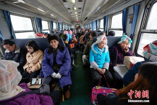 """1月17日,在开往贵阳的5639次列车坐满出行的少数民族民众。往返于贵州省贵阳市与铜仁市玉屏县的5639/5640次普速列车,全程342公里,行驶7个多小时,是人们常提到的""""绿皮火车"""",从1975年全线通车至今,这列火车已开行44年。在过去22年间,从未提高票价,区间内最低票价2元。列车穿行于贵州山区,沿线16个站连通很多少数民族村寨,目前仍是沿线民众赶集买卖,进城办事的重要交通工具。2019年春运期间,贵阳客运段5639/5640次、5629/5630次、5645/5646次列车不停运,方便沿线民众出行。中新社记者 贺俊怡 摄"""