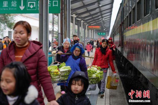 """1月17日,贵州凯里火车站,菜农挑着蔬菜前往销售市场。往返于贵州省贵阳市与铜仁市玉屏县的5639/5640次普速列车,全程342公里,行驶7个多小时,是人们常提到的""""绿皮火车"""",从1975年全线通车至今,这列火车已开行44年。在过去22年间,从未提高票价,区间内最低票价2元。列车穿行于贵州山区,沿线16个站连通很多少数民族村寨,目前仍是沿线民众赶集买卖,进城办事的重要交通工具。2019年春运期间,贵阳客运段5639/5640次、5629/5630次、5645/5646次列车不停运,方便沿线民众出行。中新社记者 贺俊怡 摄"""