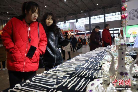 1月19日,两位市民在选购银饰。当日,临近春节,在2019贵阳新春年货购物节上前来选购年货的民众络绎不绝。 中新社记者 瞿宏伦 摄