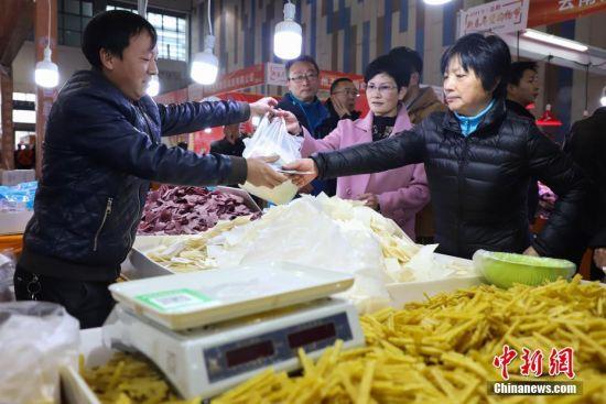 1月19日,民众在购买干粮类商品。当日,临近春节,在2019贵阳新春年货购物节上前来选购年货的民众络绎不绝。 中新社记者 瞿宏伦 摄