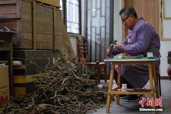 """1月19日,贵州清镇,李坤望在工作室内一堆废弃树根前挑选用材,开始一天的工作。今年68岁的李坤望,人称""""根痴"""",于1992年初下岗后,开始有意识搜集被废弃的树根,根据树根的自然形态,用传统木匠工艺""""榫卯结构"""",构建成原书法、绘画作品墨迹走势及神韵的艺术门类。2004年,李坤望将其独创的作品命名为""""墨迹根书、画""""。在他的工作室里,一幅宽500厘米、高250厘米、重220公斤的巨型""""墨迹根书""""《沁园春·雪》是他的代表作,这幅墨迹根书失真率小于5%,他整整花了26个月的时间进行创作。中新社记者 贺俊怡 摄"""