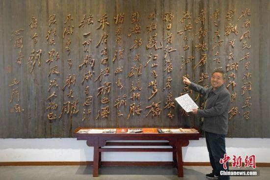 """1月19日,贵州清镇,李坤望在工作室内向到访的参观者介绍其巨型""""墨迹根书""""代表作《沁园春·雪》。今年68岁的李坤望,人称""""根痴"""",于1992年初下岗后,开始有意识搜集被废弃的树根,根据树根的自然形态,用传统木匠工艺""""榫卯结构"""",构建成原书法、绘画作品墨迹走势及神韵的艺术门类。2004年,李坤望将其独创的作品命名为""""墨迹根书、画""""。在他的工作室里,一幅宽500厘米、高250厘米、重220公斤的巨型""""墨迹根书""""《沁园春·雪》是他的代表作,这幅墨迹根书失真率小于5%,他整整花了26个月的时间进行创作。中新社记者 贺俊怡 摄"""