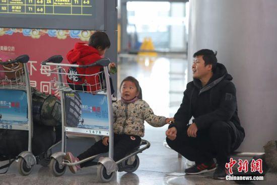 1月21日,为期40天的2019年春运启幕。据悉,当日贵阳龙洞堡国际机场预计完成航班起降460余架次,预计旅客吞吐量达5.9万余人次。图为一位父亲带着孩子等待取票的母亲,他们将从贵阳返回家乡河南。中新社记者 瞿宏伦 摄