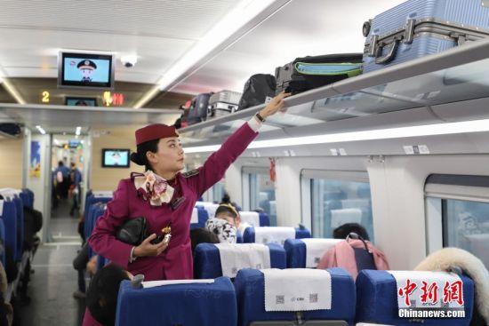 1月19日,伏玲在整理车厢内的行李架。今年27岁的伏玲,是中国铁路总公司成都局集团有限公司贵阳客运段动车二队列车长,她在铁路系统已经工作5年,是贵州首批动车乘务员,并于2016年取得动车列车长资质。伏玲主要有开车前的引导、巡视车厢、检查危险品等值乘工作。2019年春运临近,加开列车和旅客数量将增多,届时,她的工作量加大。她说,她已做好春运服务工作的准备,将用心服务好旅客,让旅客能够平平安安回家。中新社记者 瞿宏伦 摄
