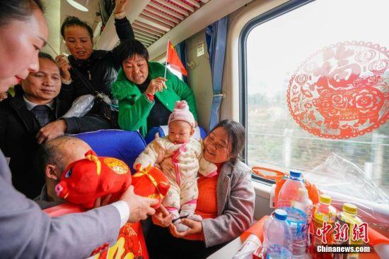 """1月22日,工作人员给小朋友送猪年吉祥物。当日,主题为""""接您回家过年――五送进车厢""""暨""""贵州务工人员返乡号""""列车活动在上海南开往贵阳的K111次列车上举行。""""五送进车厢""""即:列车专场招聘会、就业指导帮扶、就业创业技能培训、亲情驿站服务、老乡大盒饭用餐补贴和新春祝福进车厢活动。中新社记者 贺俊怡 摄"""