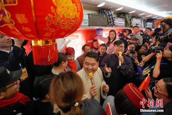"""1月22日,工作人员在列车上表演相声节目。当日,主题为""""接您回家过年――五送进车厢""""暨""""贵州务工人员返乡号""""列车活动在上海南开往贵阳的K111次列车上举行。""""五送进车厢""""即:列车专场招聘会、就业指导帮扶、就业创业技能培训、亲情驿站服务、老乡大盒饭用餐补贴和新春祝福进车厢活动。中新社记者 贺俊怡 摄"""