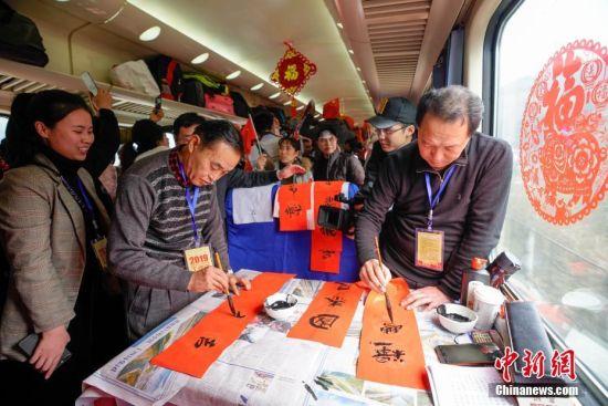 """1月22日,工作人员在列车上写春联。当日,主题为""""接您回家过年――五送进车厢""""暨""""贵州务工人员返乡号""""列车活动在上海南开往贵阳的K111次列车上举行。""""五送进车厢""""即:列车专场招聘会、就业指导帮扶、就业创业技能培训、亲情驿站服务、老乡大盒饭用餐补贴和新春祝福进车厢活动。中新社记者 贺俊怡 摄"""