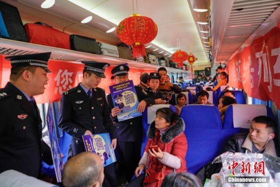 """1月22日,贵阳铁路公安处乘警向乘客进行法制宣传。当日,主题为""""接您回家过年――五送进车厢""""暨""""贵州务工人员返乡号""""列车活动在上海南开往贵阳的K111次列车上举行。""""五送进车厢""""即:列车专场招聘会、就业指导帮扶、就业创业技能培训、亲情驿站服务、老乡大盒饭用餐补贴和新春祝福进车厢活动。中新社记者 贺俊怡 摄"""