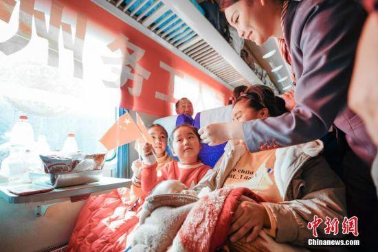 """1月22日,列车工作人员与小朋友进行游戏互动。当日,主题为""""接您回家过年――五送进车厢""""暨""""贵州务工人员返乡号""""列车活动在上海南开往贵阳的K111次列车上举行。""""五送进车厢""""即:列车专场招聘会、就业指导帮扶、就业创业技能培训、亲情驿站服务、老乡大盒饭用餐补贴和新春祝福进车厢活动。中新社记者 贺俊怡 摄"""