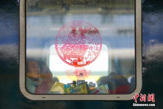 """1月22日,车窗上贴着农历猪年吉祥窗贴,迎接在外务工者回家过年。当日,主题为""""接您回家过年――五送进车厢""""暨""""贵州务工人员返乡号""""列车活动在上海南开往贵阳的K111次列车上举行。""""五送进车厢""""即:列车专场招聘会、就业指导帮扶、就业创业技能培训、亲情驿站服务、老乡大盒饭用餐补贴和新春祝福进车厢活动。中新社记者 贺俊怡 摄"""