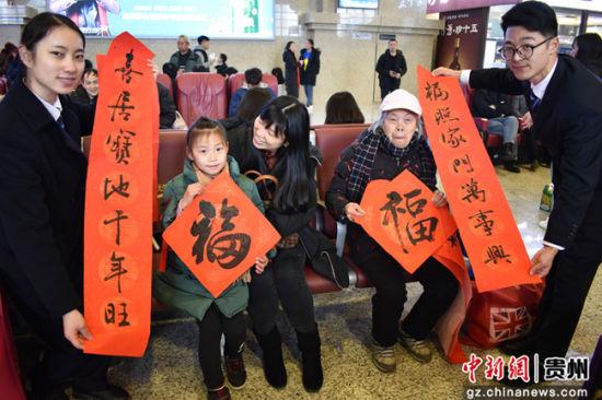 图为遵义站工作人员向旅客赠送现场书写的春联。