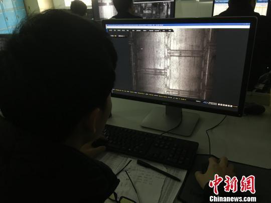 中国铁路成都局集团有限公司贵阳车辆段贵阳北动车运用所TEDS检测中心,TEDS分析员仔细浏览TEDS探测设备传回的一张张动车部件图片,从中发现故障和隐患,为动车组安全运行保驾护航。 周娴 摄